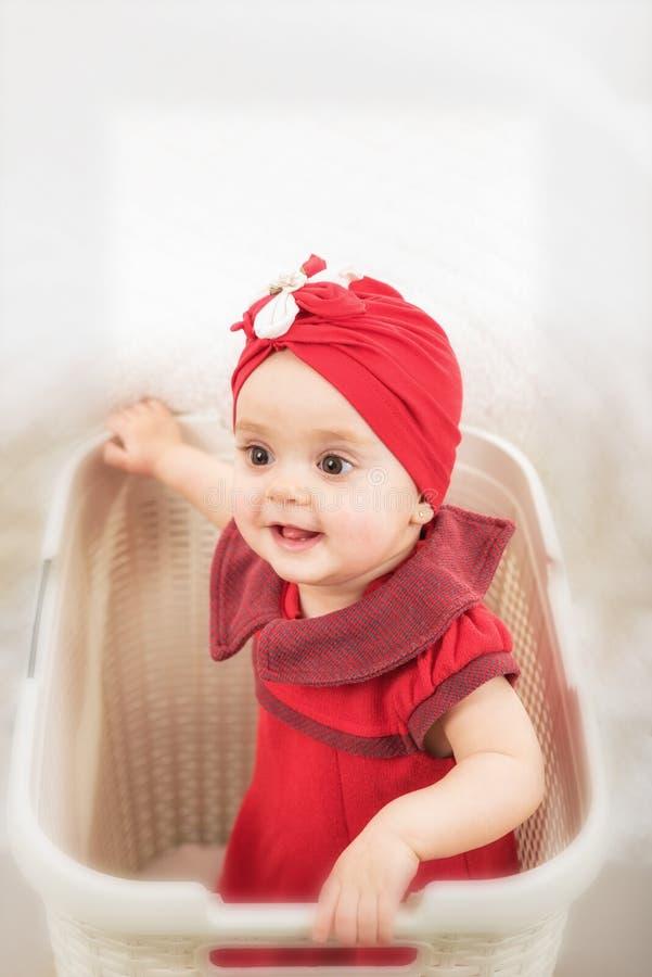 女婴上部画象到洗衣篮里 免版税图库摄影