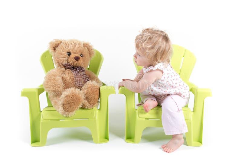 女婴与她的玩具熊谈话 库存图片