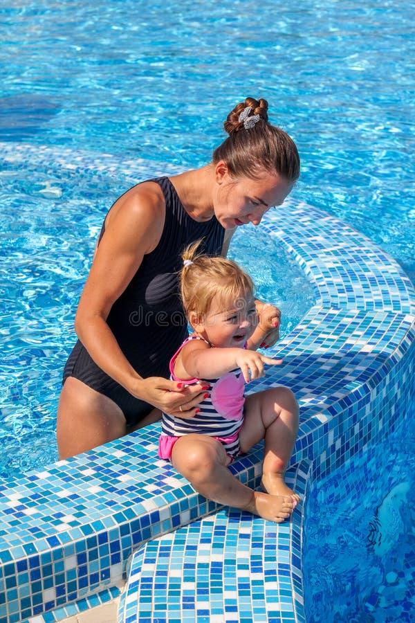 女婴在与她的母亲的水池学会游泳 库存照片