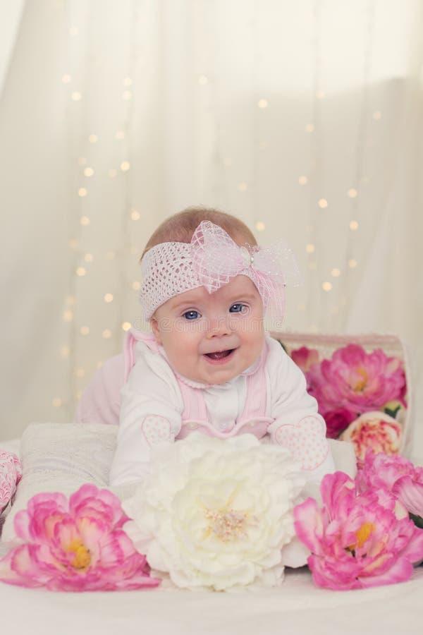 女婴在与桃红色花的床上 免版税库存照片