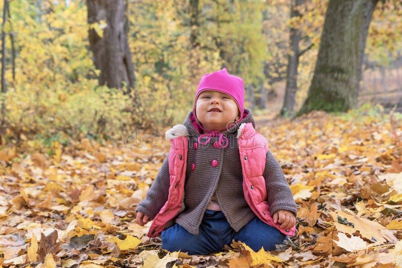 女婴在秋天公园做鬼脸 免版税库存图片