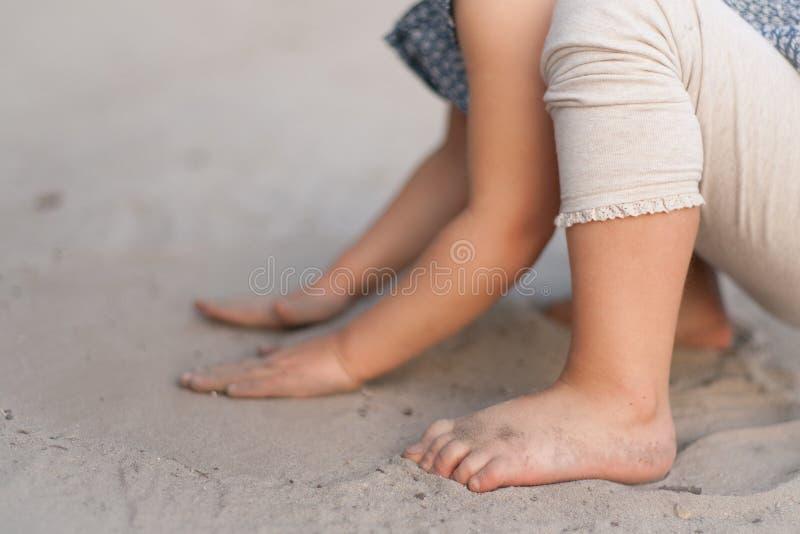 女婴坐使用与沙子的海滩 免版税图库摄影