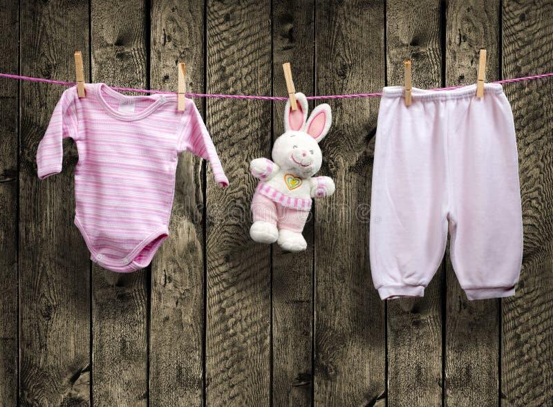 女婴衣裳和兔宝宝在晒衣绳 库存图片