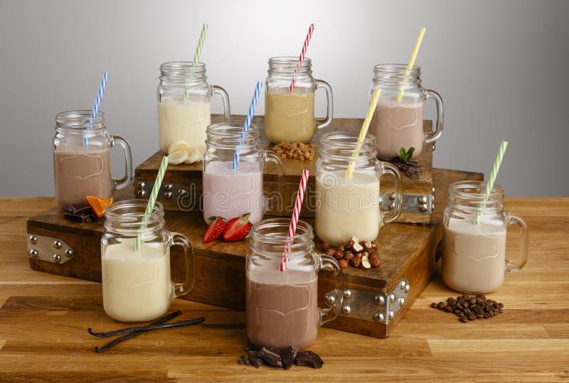 奶昔和成份的各种各样的类型在金属螺盖玻璃瓶玻璃与纸秸杆在木台式 免版税库存图片