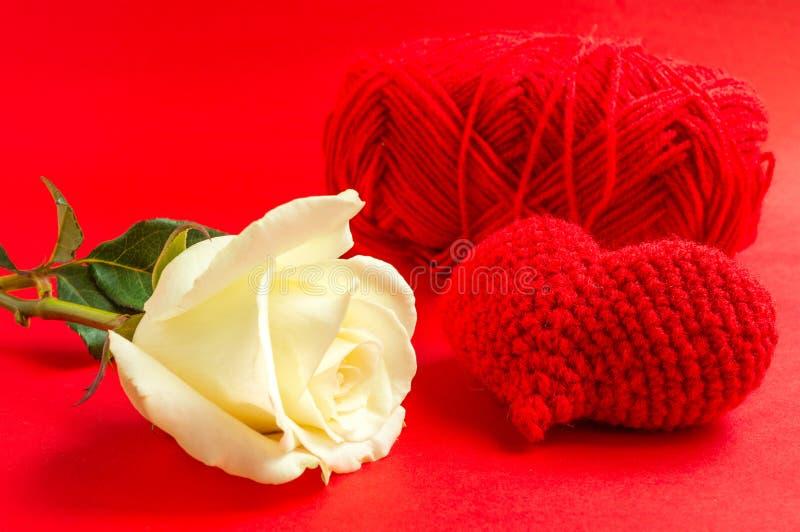 奶油上升了与在红色背景的红色心脏钩针编织 库存图片