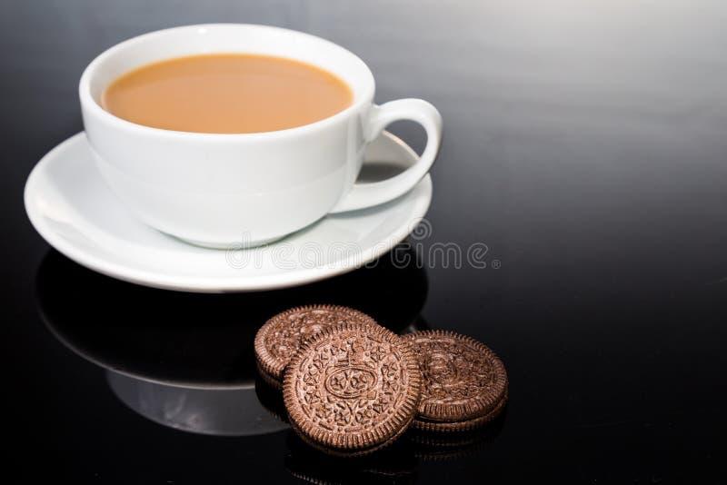奶油充满的三明治曲奇饼和牛奶咖啡在黑暗的反射性背景 免版税库存照片