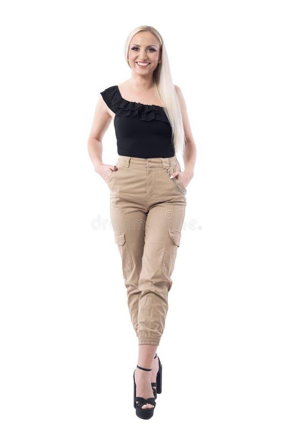 奶油色军用摆在照相机的裤子和黑上面的美丽的愉快的微笑的白肤金发的妇女 库存图片