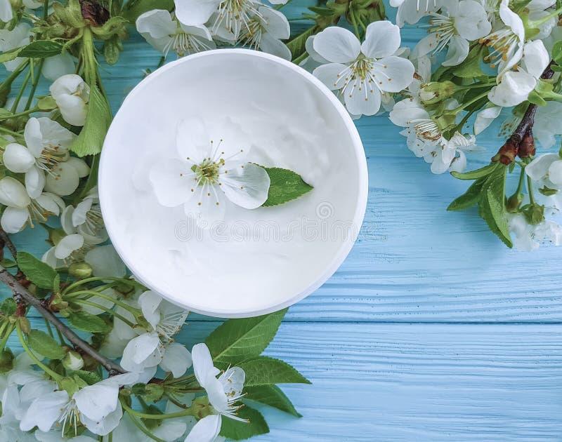 奶油色化妆在蓝色木背景的不老长寿药面具有机治疗健康开花的樱桃 库存图片