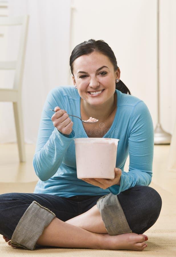 奶油色吃的冰妇女 库存图片