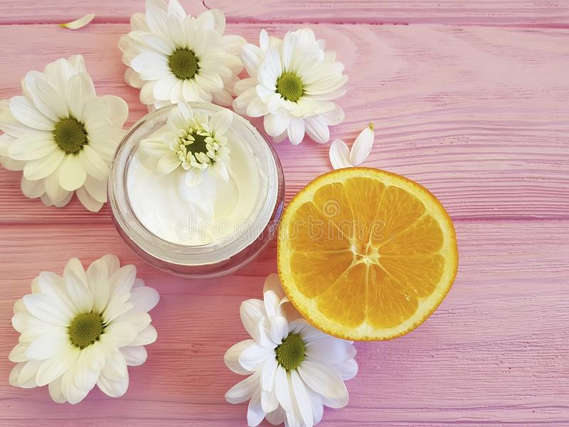 奶油色有机化妆在一棵桃红色木春黄菊的瓣橙色手工制造明亮的构成健康白花在蓝色木 库存照片