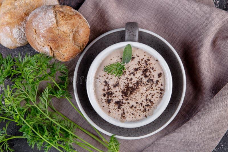 奶油色汤用新草本和卷在杯子 库存照片