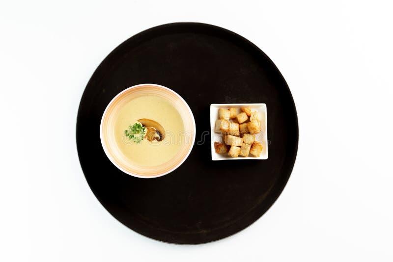 奶油色汤用蘑菇和草本和薄脆饼干在一个圆的盘子在被隔绝的白色背景 库存照片