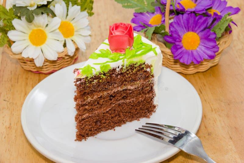 奶油色蛋糕与在木桌上上升了 免版税图库摄影