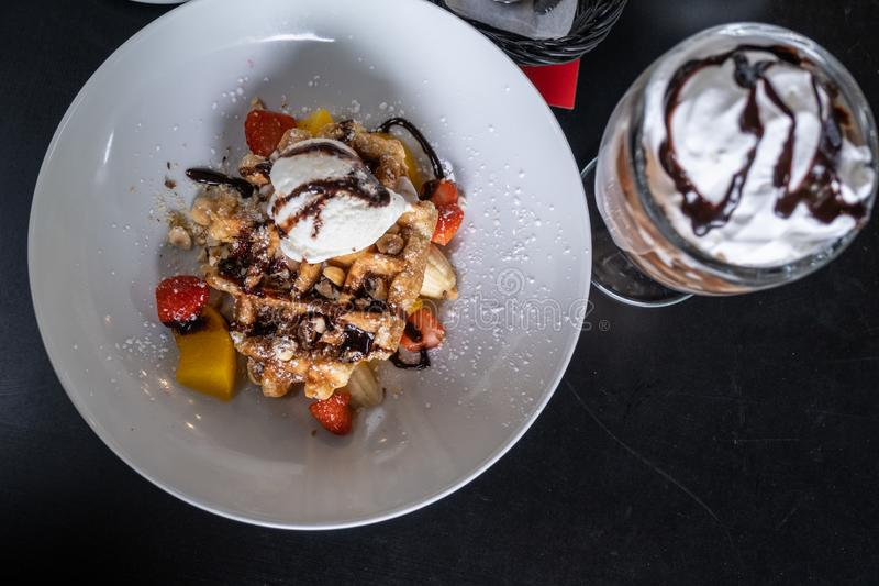 奶蛋烘饼与涂了巧克力的冰淇淋和装饰用在一块板材的果子在桌上 免版税库存图片