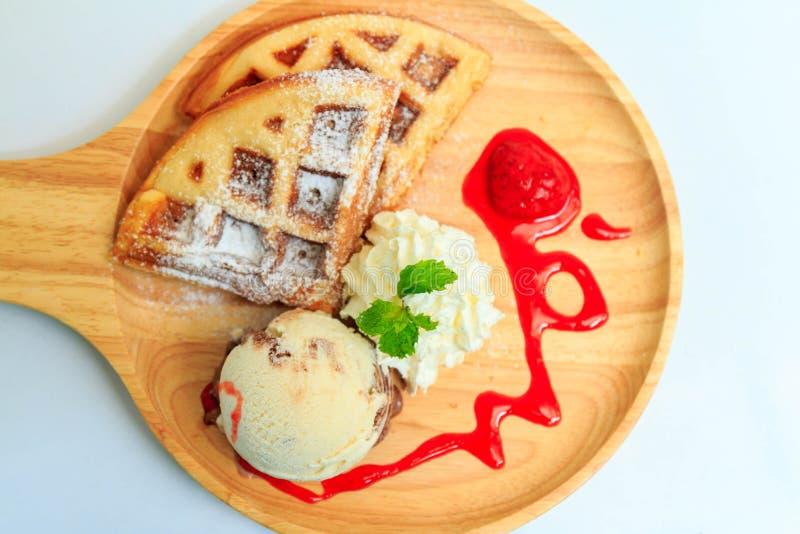 奶蛋烘饼冰淇凌和打好的奶油在一个木盘子服务 图库摄影