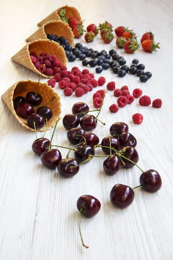 奶蛋烘饼甜冰淇凌用莓、樱桃、草莓和蓝莓在白色木背景 库存照片