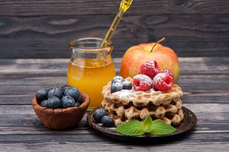 奶蛋烘饼用莓果、果子和蜂蜜 库存图片