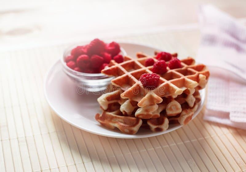 奶蛋烘饼用蜂蜜、果酱和莓果在一块白色板材 库存照片