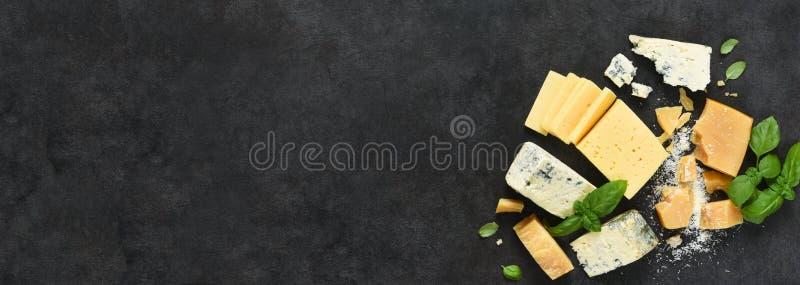 奶酪集:黑色水泥背景中的奶油色、蓝色奶酪、干酪和罗勒 从上方查看 库存图片