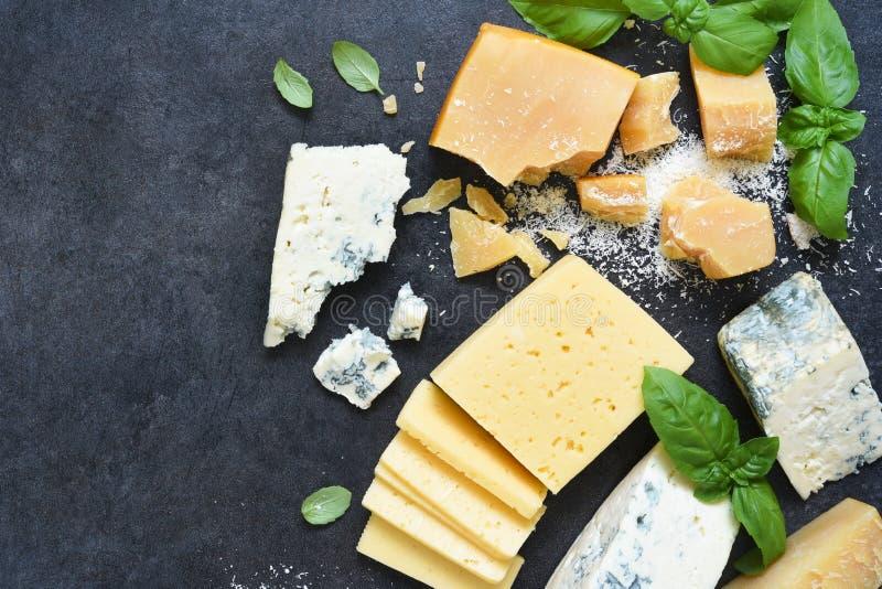 奶酪集:黑色水泥背景中的奶油色、蓝色奶酪、干酪和罗勒 从上方查看 库存照片