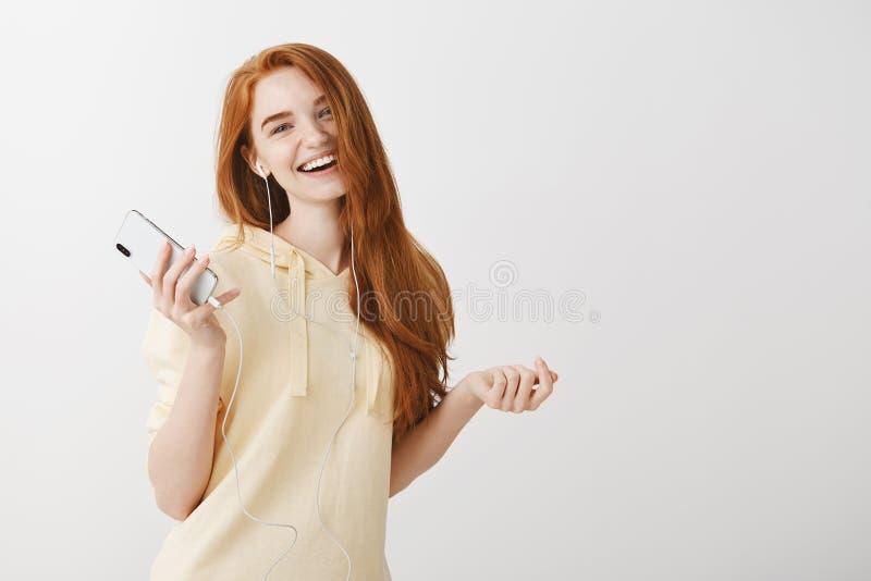 她发现了她的心情电影配乐  正面悦目女孩,藏品智能手机画象有姜头发跳舞的 免版税图库摄影