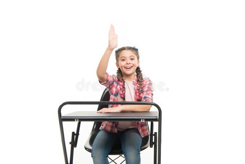 她吸取了教训 逗人喜爱的小学生用坐在学校书桌的被举的手 一点女小学生背诵的教训在 免版税图库摄影