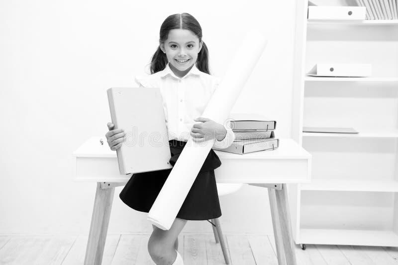 她喜欢创造性的任务 女孩儿童举行文件夹和whatman纸,当立场桌白色内部时 孩子校服 免版税图库摄影