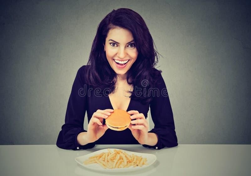 她喜欢快餐 吃乳酪汉堡和炸薯条的愉快的少妇 免版税库存照片