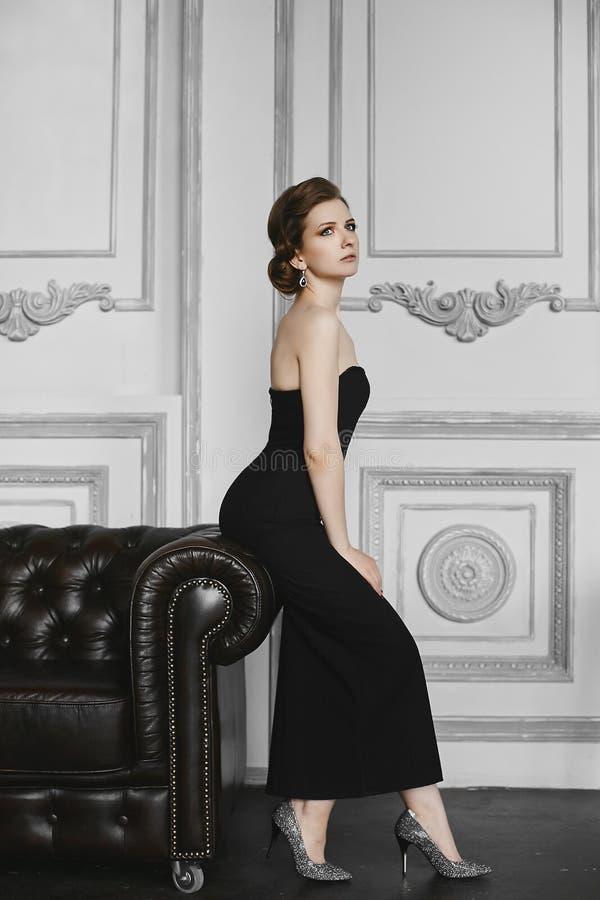 她在沙发葡萄酒沙发和摆在倾斜在的长的黑礼服的时兴,性感和美丽的深色的式样女孩 库存图片