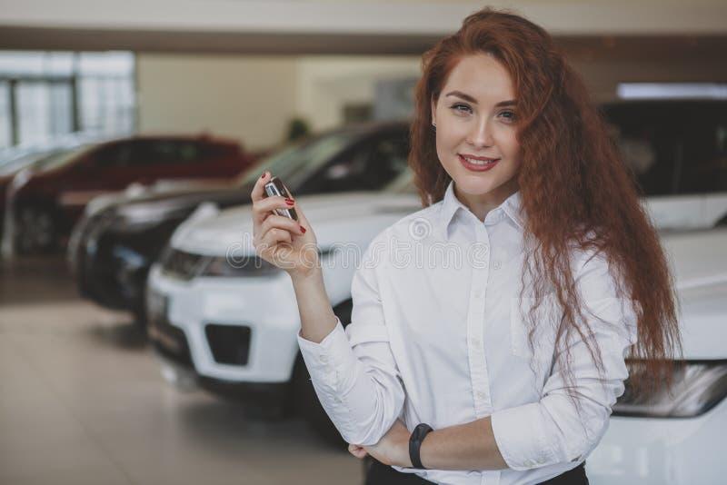 她新的汽车的愉快的妇女藏品汽车钥匙 免版税库存图片