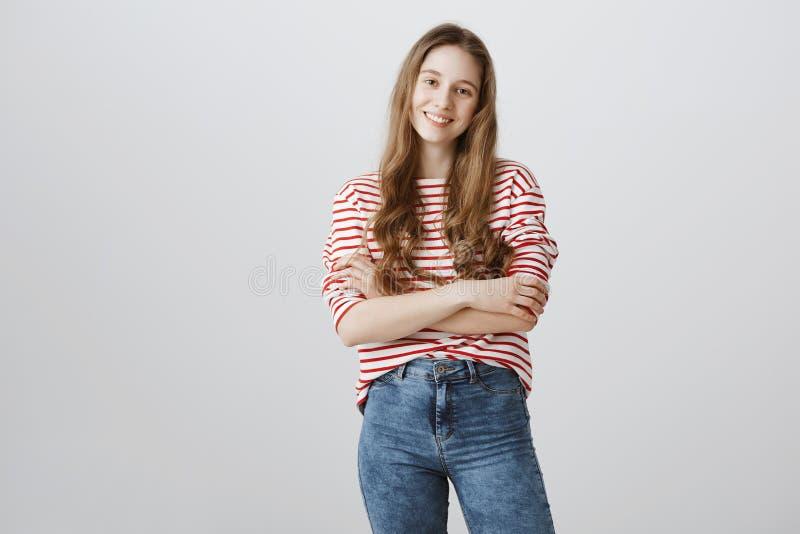 她是年轻,但是已经自信的 演播室射击了有站立与的金发的确信的美丽的十几岁的女孩 免版税图库摄影