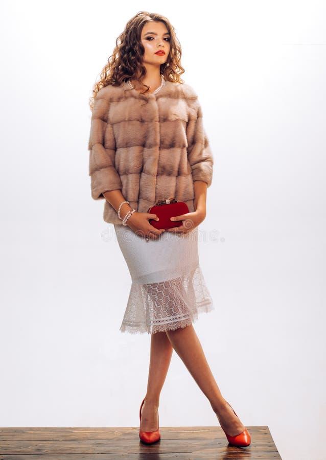 她是漂泊在态度 年轻女人穿典雅的冬天外套 为冬天寒冷完善 俏丽的妇女 免版税库存图片