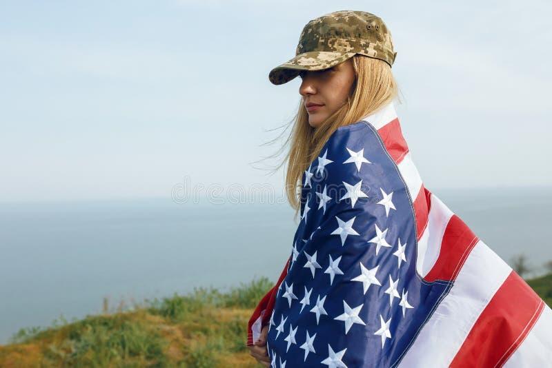 她的丈夫的军用盖帽的民用妇女 有美国的旗子的一个寡妇离开,不用她的丈夫 阵亡将士纪念日 免版税库存照片