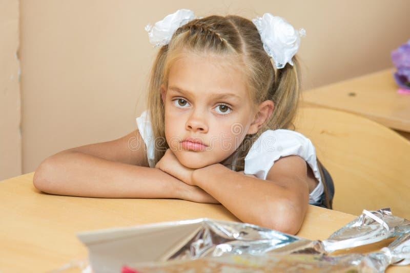 她的书桌的一个哀伤的女孩在教训9月一日 免版税库存图片