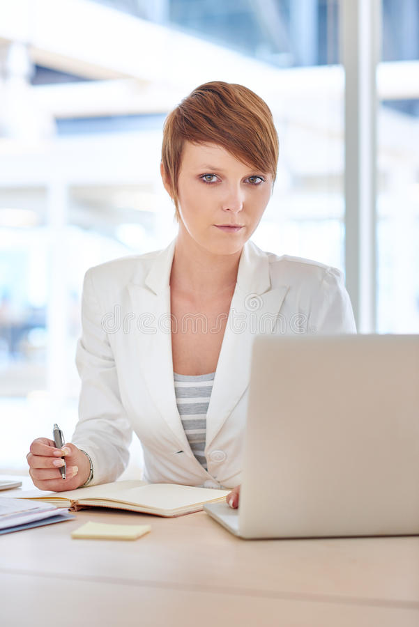 她的书桌的严肃的年轻女实业家有膝上型计算机的 免版税库存照片