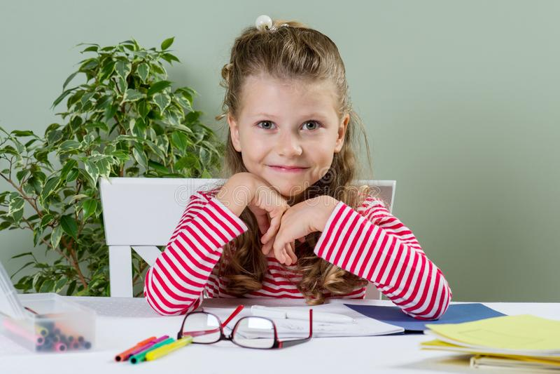 她的书桌的小迷人的女小学生有书的,笔记本,铅笔,回到学校和愉快的时间 免版税库存图片
