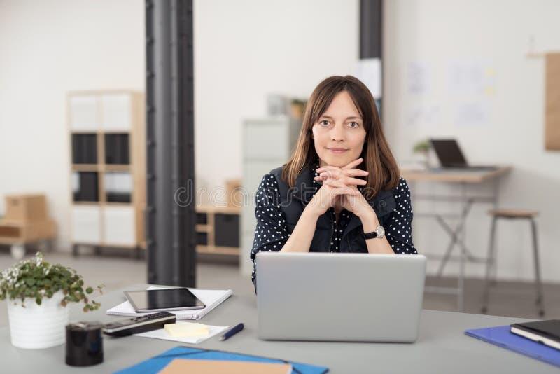 她的倾斜在她的手的书桌的办公室妇女 库存照片
