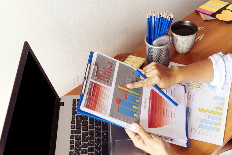 她的办公桌的聪明的职业妇女有文件和膝上型计算机的 工作在文书工作的女实业家 免版税库存照片