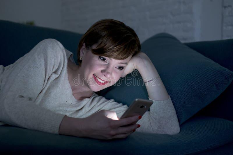 她的后说谎在家庭长沙发的20s的年轻俏丽和愉快的红色头发妇女或30s或床使用手机在夜微笑的relaxe 库存照片
