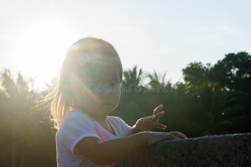 洗她的在喷泉的美丽的小女孩手 在日落 严肃的周道的面孔 免版税图库摄影