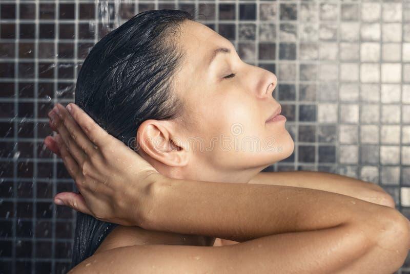 洗她的在阵雨的可爱的妇女头发 免版税库存图片