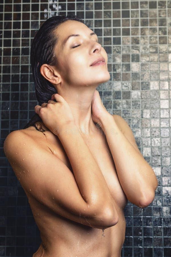 洗她的在阵雨的可爱的妇女头发 库存图片
