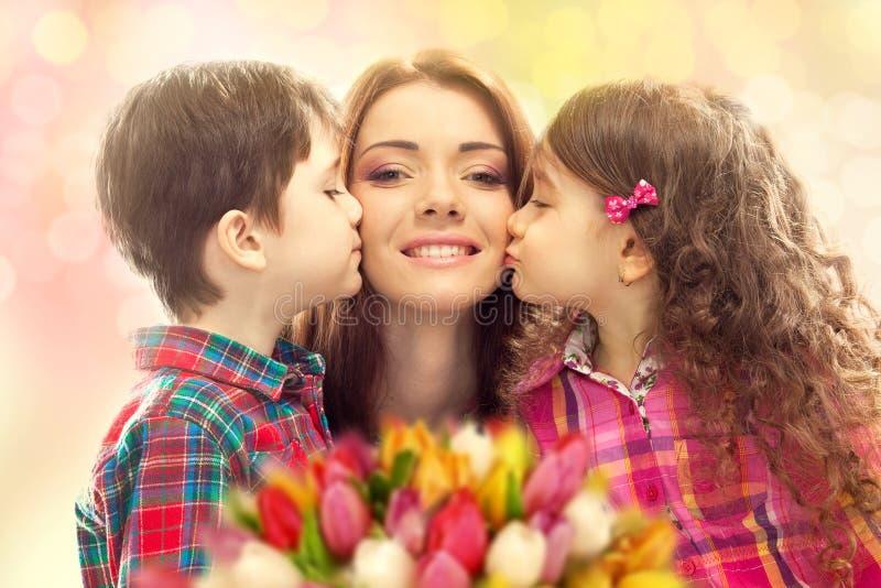 她的女儿和儿子亲吻的愉快的母亲 免版税库存照片
