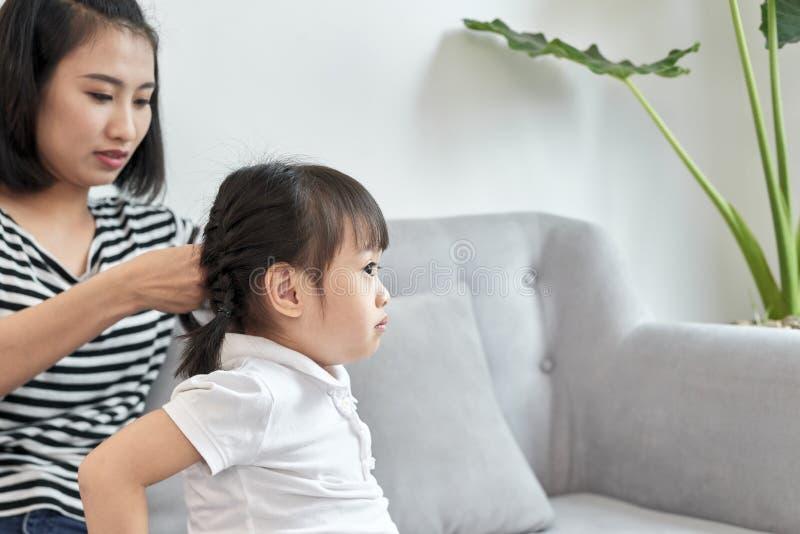 她的女儿的母亲把编成辫子的头发 免版税库存图片