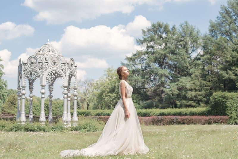 她的婚礼礼服柔和的空气的美丽的嫩少妇新娘在繁茂花园里走在一个热的晴朗的夏日 免版税图库摄影