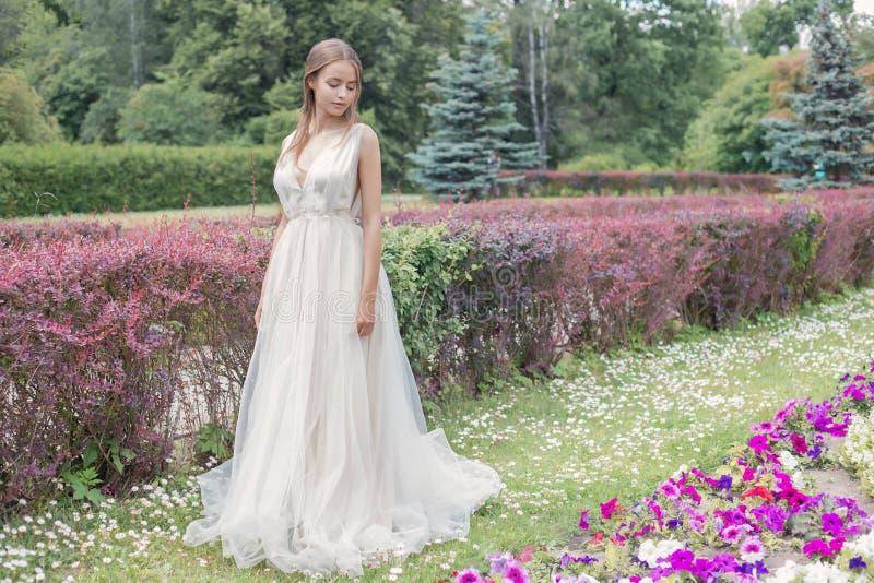 她的婚礼礼服柔和的空气的美丽的嫩少妇新娘在繁茂花园里走在一个热的晴朗的夏日 图库摄影
