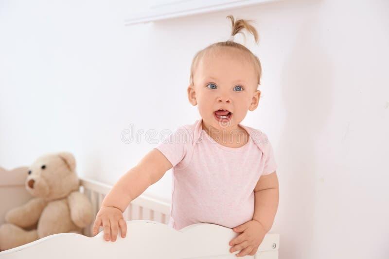 她的小儿床的可爱的女婴 库存照片