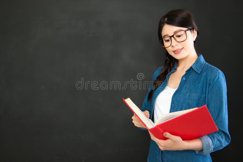 读她的工作的亚洲学生站立在黑板前面 免版税库存图片