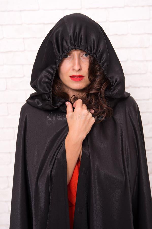 她的巫婆姐妹将是羡慕的 一个邪恶的巫婆 白色砖的万圣节巫婆 神奇夫人打扮  图库摄影