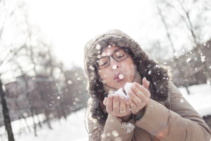 从她的手的妇女吹的雪花 免版税库存图片